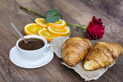 Croissants with butter ,cup of coffee and orange  for breakfast Royalty Free Stock Image