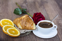 Croissants with butter ,cup of coffee,rose and orange  for breakfast, Royalty Free Stock Photography