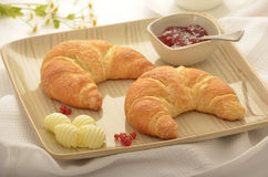 Croissants with butter and jam. Golden flaky croissants with butter curls and strawberry red currant jam.  Selective focus on tip of foremost croissant Stock Photos