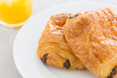 Croissants with chocolate filling on a white plate, orange juice on a white tray Royalty Free Stock Photos