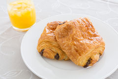 Croissants with chocolate filling on a white plate, orange juice on a white tray Stock Image
