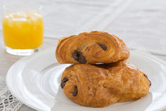 Croissants with chocolate filling on a white plate, orange juice on a white tray Royalty Free Stock Photography