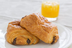 Croissants with chocolate filling on a white plate, orange juice on a white tray Royalty Free Stock Images
