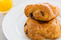 Croissants with chocolate filling on a white plate, orange juice on a white tray Royalty Free Stock Photo