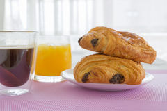 Croissants with chocolate filling on a white plate, orange juice on a white tray Stock Photo