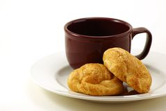 Croissants and Coffee. Butter Croissant pastries on white plate with brick red marroon colored coffee cup behind. White background with copy space. Moderate Stock Photos