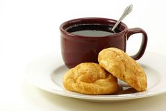 Croissants and Coffee. Butter Croissant pastries on white plate with brick red marroon colored coffee cup behind. A silver spoon is in the coffee. White Stock Images