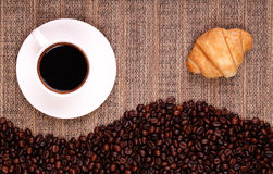 Croissants coffee and beans on the table Royalty Free Stock Photography
