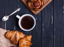Croissants and coffee in the black wooden table. Top view royalty free stock photo