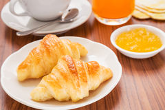 Croissants, coffee cup and juice on wooden table Royalty Free Stock Photo