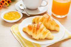 Croissants, coffee cup and juice on wooden table royalty free stock photography