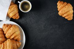 Croissants and coffee on a dark background. Breakfast flat lay stock photo