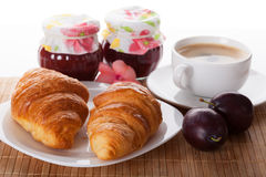 Croissants coffee and jam. Two croissants, two jars of jam and a cup of coffee Royalty Free Stock Photos