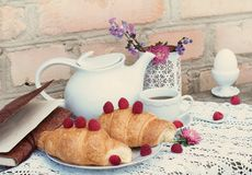 Croissants with coffee and raspberry on white a lace tablecloth Royalty Free Stock Photography