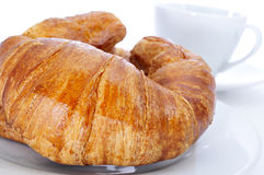 Croissants and coffee. Some croissants on a plate and a cup of coffee on a white background royalty free stock photos