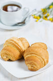 Croissants with cup of tea Stock Photos