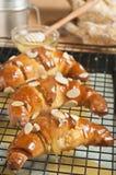 Croissants d'amande fraîchement cuits au four de miel se refroidissant sur la grille photos stock