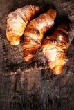 Croissants d'or frais sur le fond rustique foncé Photographie stock libre de droits