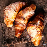 Croissants d'or frais sur le fond rustique foncé Photo stock
