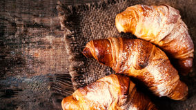 Croissants d'or frais sur le macro rustique foncé d'extrémité de fond Image stock