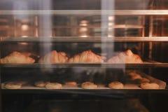 Croissants die in oven bakken Productieoven bij de bakkerij Bakselbrood Vervaardiging van brood stock afbeeldingen