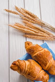 Croissants and ears of wheat on white wooden Stock Image