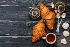 Croissants en cake met bosbessen op een oude rustieke achtergrond Thee, uitstekend lepel en schuimgebakje Hoogste mening royalty-vrije stock afbeelding