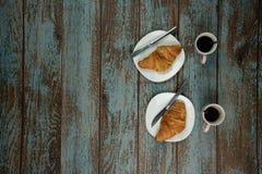 Croissants fraîchement cuits au four avec du café sur un fond en bois de vieux cru avec l'espace ? c?t? de lui pour le texte photos stock