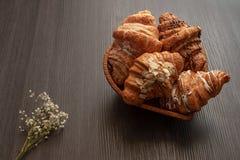 Croissants fraîchement cuits au four avec les amandes, le chocolat et le sucre en poudre sur une vue supérieure foncée en bois de image stock