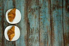 Croissants fraîchement cuits au four d'un plat blanc Fond en bois de vieux cru avec l'espace de copie pour votre propre texte images stock