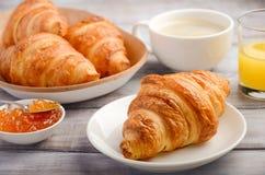 Croissants frais avec du café, la confiture et le jus d'orange pour le petit déjeuner sur le fond en bois rustique Image libre de droits