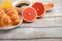 Croissants frais avec du café, la confiture et le jus d'orange pour le petit déjeuner sur le fond en bois rustique Photo stock