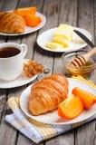 Croissants frais avec le kaki et la tasse de thé Images libres de droits