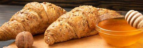 Croissants frais avec le pot et les écrous de miel photos libres de droits