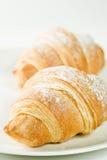 Croissants frais de la plaque blanche avec du sucre en poudre Photos libres de droits