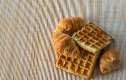 Croissants frais et gaufres délicieuses sur le tapis en bambou, boulangerie Images stock