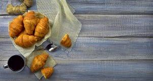 Croissants frais et une tasse de café/de thé sur un vieux tabl en bois Photos stock