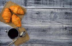 Croissants frais et une tasse de café/de thé sur une vieille table en bois Vue supérieure de petit déjeuner Photo libre de droits