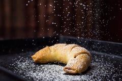 Croissants frais savoureux arrosés avec du sucre en poudre C délicieux images libres de droits