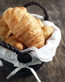 Croissants. Fresh Croissants in basket on wooden background Royalty Free Stock Photography