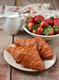 Croissants with fresh strawberries in a white plate. On wooden background stock images