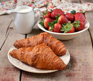Croissants with fresh strawberries in a white plate. On wooden background stock photography
