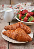 Croissants with fresh strawberries in a white plate. On wooden background royalty free stock image