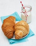 Croissants and a glass of milk. On a wooden background Stock Images