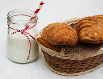 Croissants and a glass of milk. On a wooden background Royalty Free Stock Photos