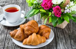 Croissants, herbata i kwiaty na starym drewnianym stole, Zdjęcia Stock