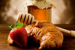 Croissants with honey and strawberries Stock Images