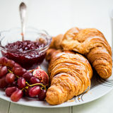 Croissants with Icing, Cup of Tea, Grapes, Sugar and Strawberry. Fresh Croissants with Cup of Tea, Milk, Sugar, Grapes and Strawberry Jam are ready for the Stock Photo