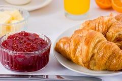 Croissants, jam, and orange juice. Stock Photography