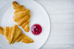 Croissants and  jam on the white ceramic plate top view Royalty Free Stock Photos
